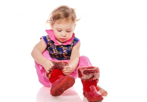 Baby putting on shoes sitting  isolated on white