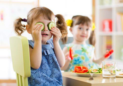 Cute kids eating healthy food in kindergarten or at home